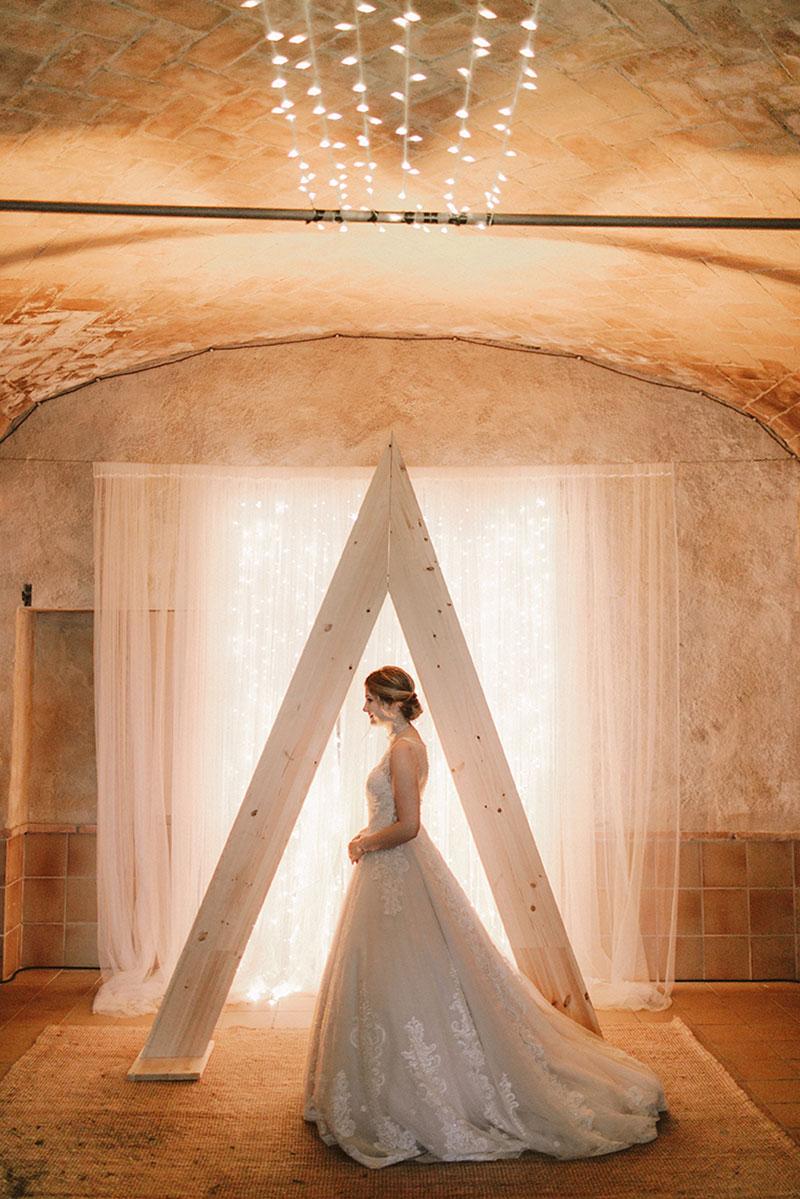 Boda interior con mucho rollo | Ceremonia Backdrop madera Flores Novios Luces | www.bodasdecuento.com