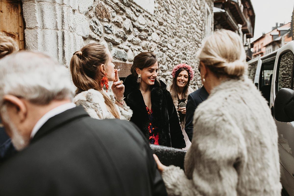 invitados con abrigos a la entrada de una boda de invierno en el pirineo