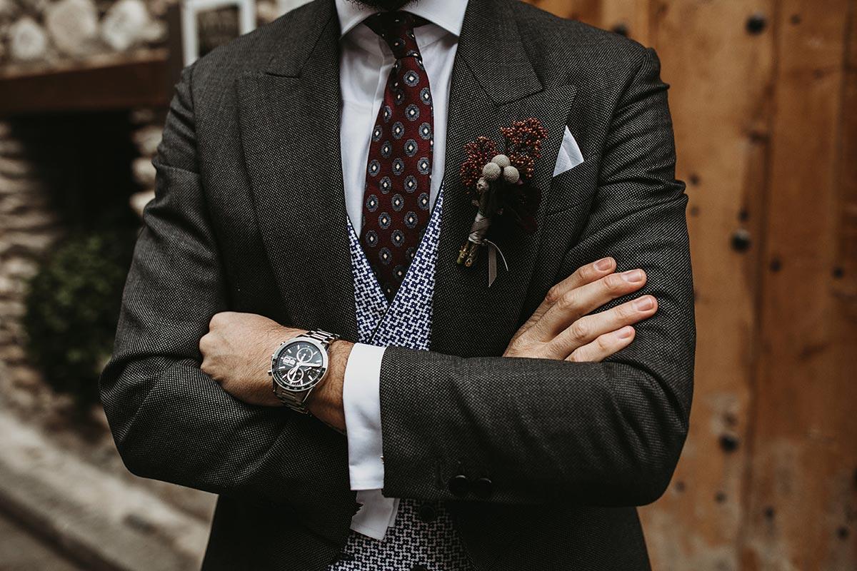 traje de novio gris corbata granate chaleco y prendido de flores