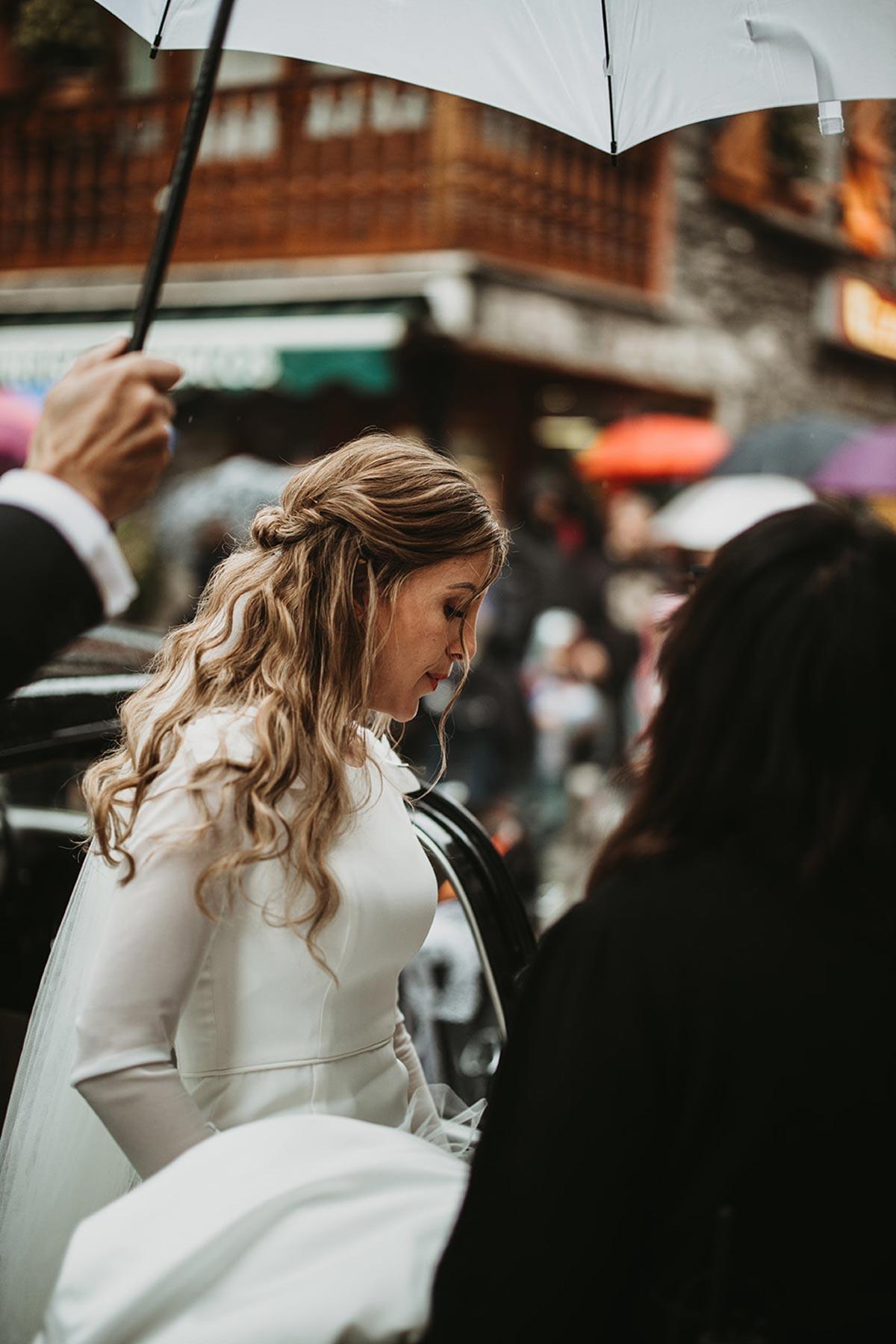Novia saliendo del coche con lluvia paraguas blanco