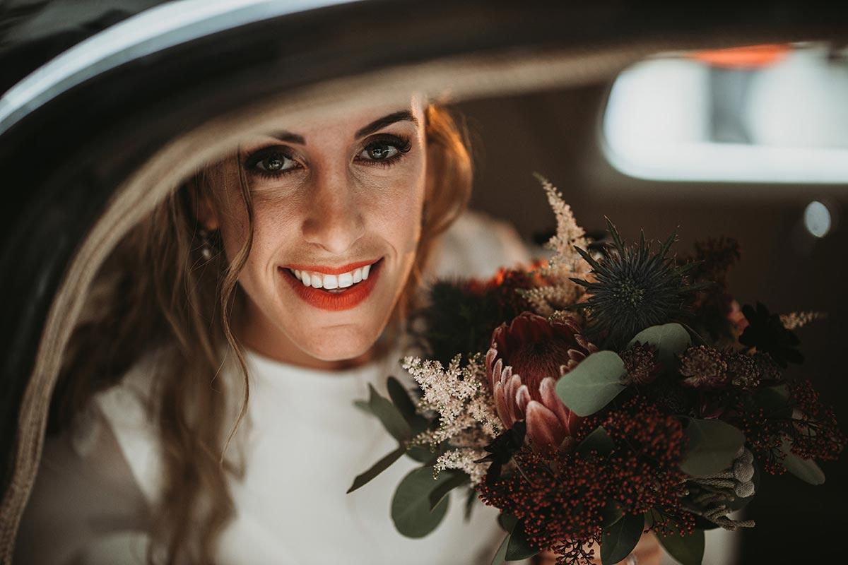 Novia sonrisa coche clásico ramo silvestre invierno