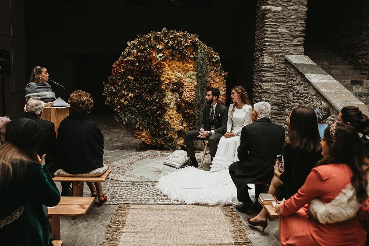 Ceremonia de boda de invierno con backdrop circular de flores con madera y velas | Bodas de Cuento Wedding Planners