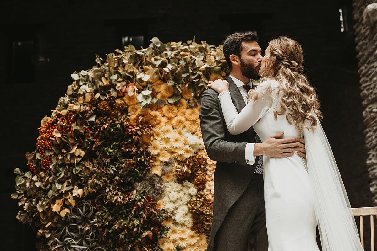 Ceremonia de boda de invierno con backdrop circular de flores novios beso