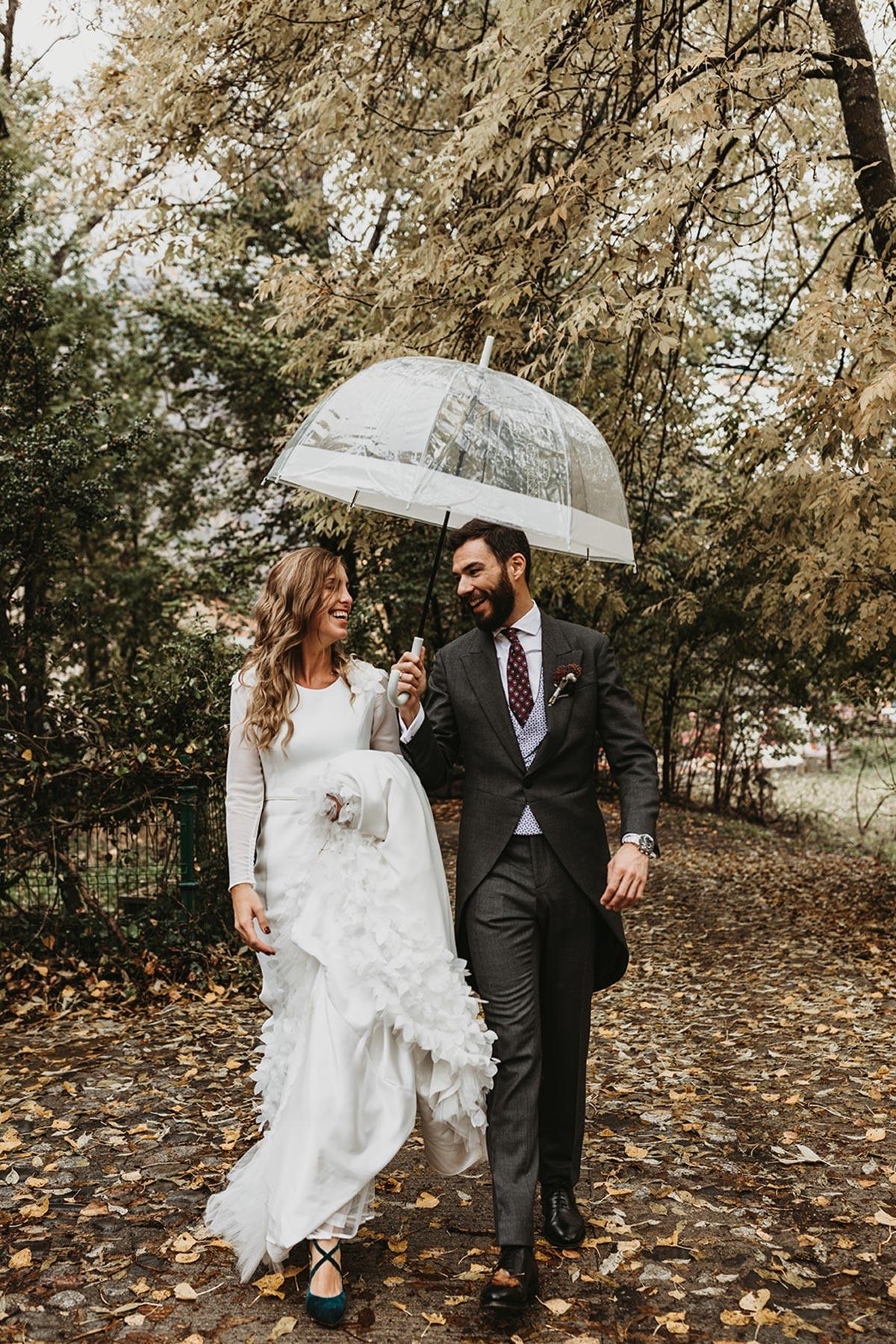 Fotografía de novios bajo la lluvia paraguas boda de invierno