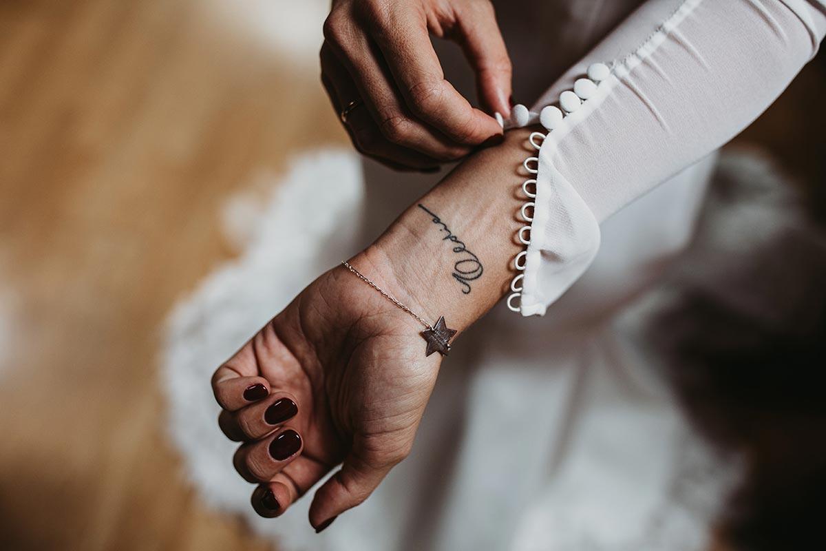 Novia con tatuaje en la muñeca manga de tul con botones