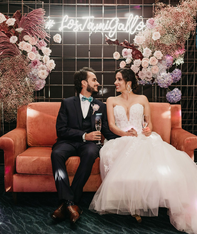 Caro y Sergio en el sofá marrón con luces de neon de fondo | Bodas de cuento